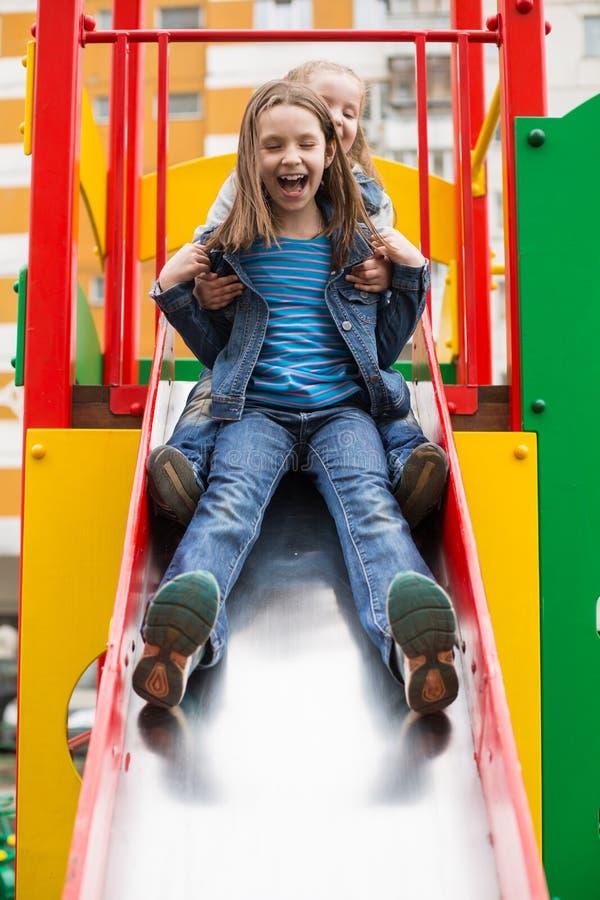 Flickor glider ner kullen på lekplatsen fotografering för bildbyråer