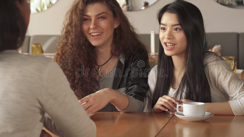 Flickor har en pratstund över en kopp kaffe på kafét royaltyfria bilder