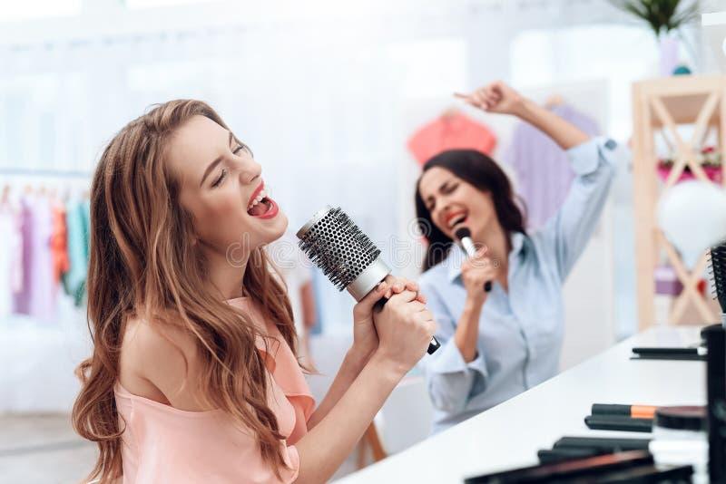 Flickor har gyckel i visningslokalen Flickor sjunger och rymmer en hårkam i deras händer fotografering för bildbyråer