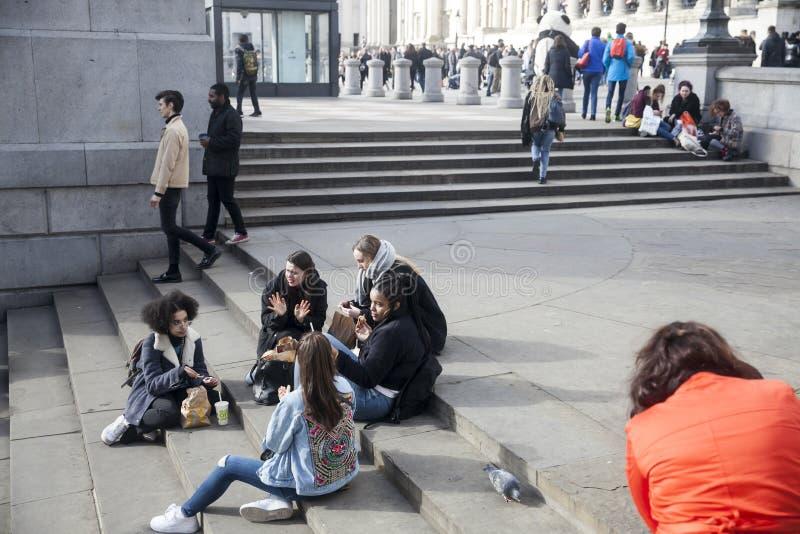 Flickor har lunch på momenten nära National Gallery på Trafalgar Square arkivfoto