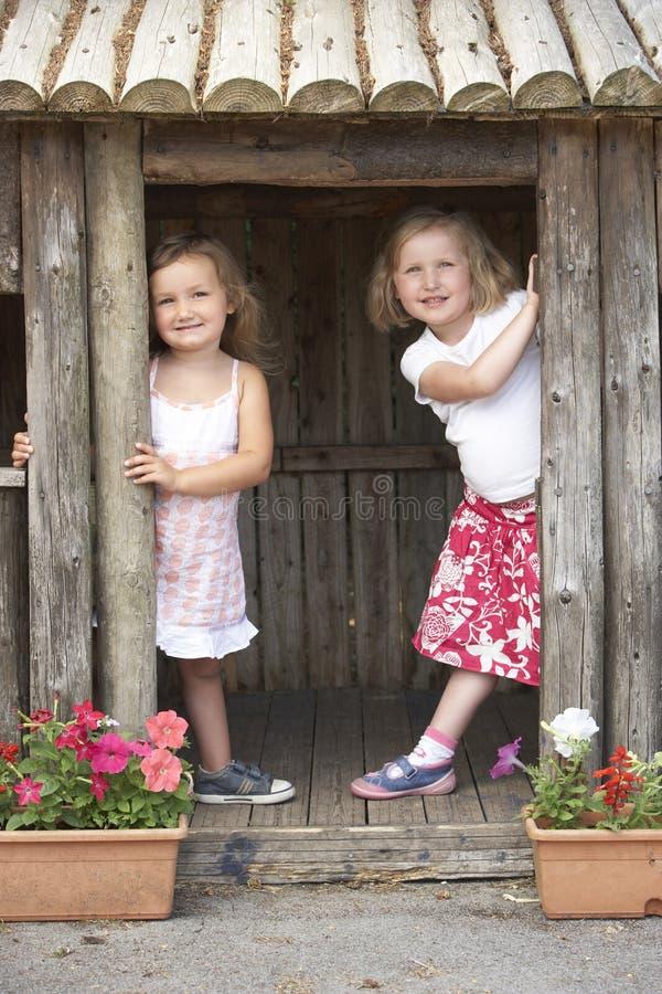 flickor house att leka två träbarn arkivfoton