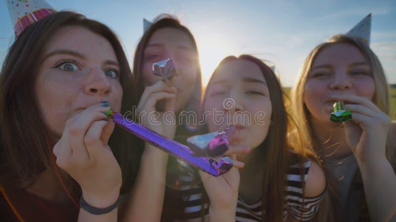 Flickor hurrar och firar ferien utomhus och blåser leker med ut lock på deras huvud royaltyfri foto