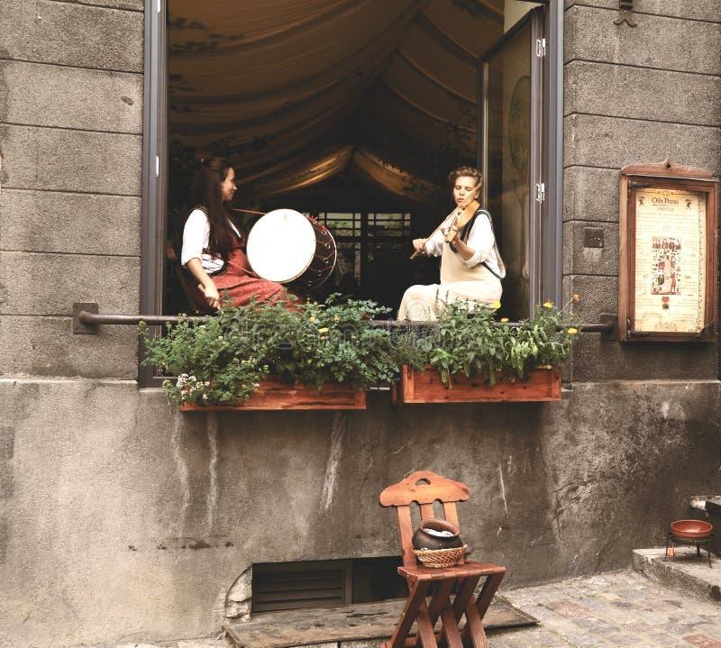Flickor i forntida estländsk kläder spelar på musikinstrument royaltyfri fotografi