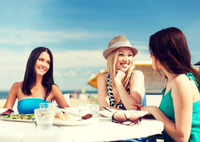 Flickor i kafé på stranden arkivfoto