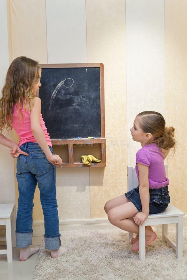 Flickor i lekrummet målar på svart tavla arkivfoto