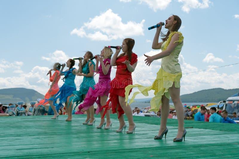 Flickor i ljusa klänningar sjunger på en trägrön etapp under den etniska Karatag festivalen på kusten av en stor sjö arkivbilder