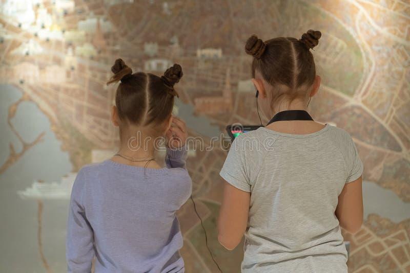 Flickor i museum som lyssnar till att intressera information om utställning till och med hörlurar ?versikt v?xelverkande arkivfoto