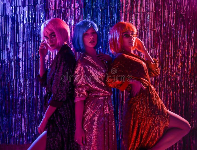 Flickor i peruker och stilfulla glamor?sa kl?nningar med paljetter, i neonljuset av ett disko Fira, ha gyckel, fira n?got arkivfoton