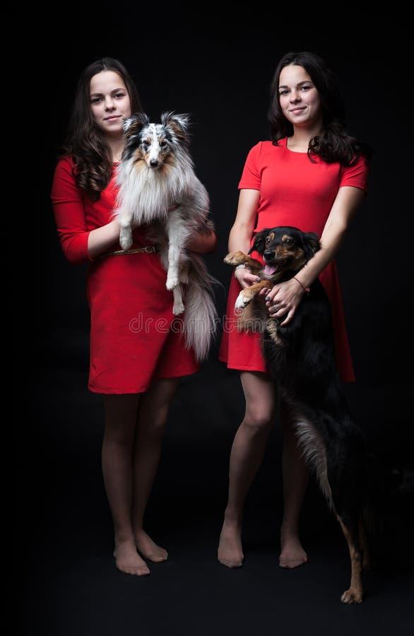Flickor i röda klänningar med hundkapplöpning på svart bakgrund royaltyfria bilder