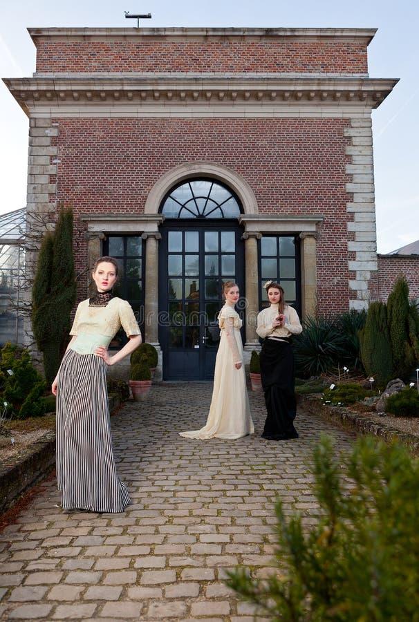 Flickor i viktorianskt framme av det gamla huset arkivfoton
