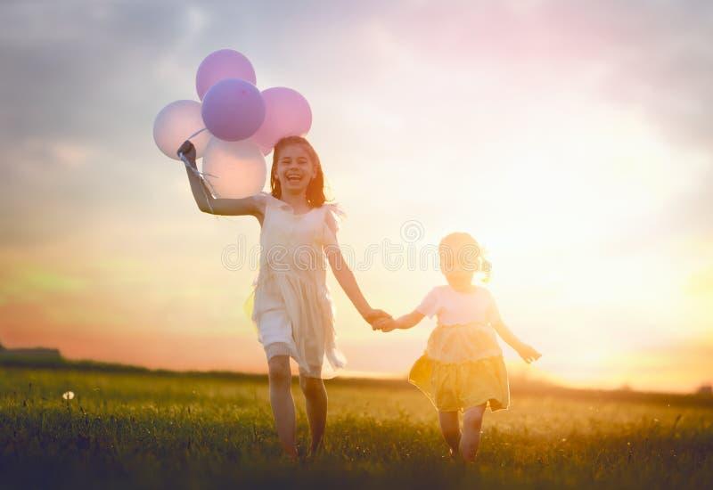 Flickor kör med luftballonger royaltyfria foton