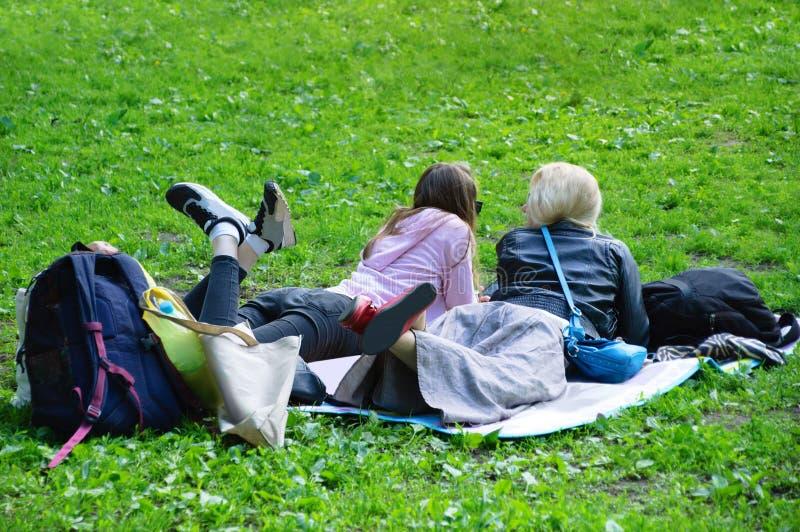 Flickor lägger på det gröna gräset i sommar Lyckligt i parken arkivbild