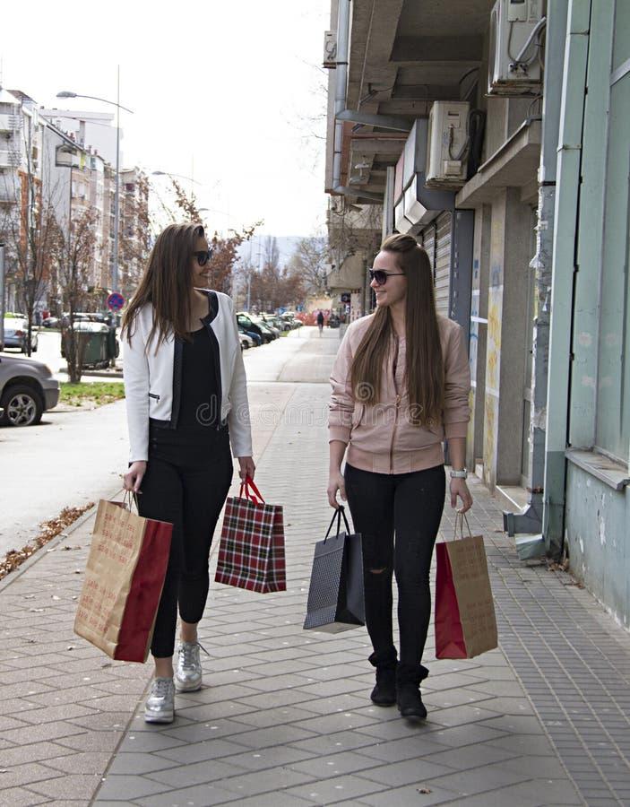 Flickor ler att gå ner gatan, når de har köpt kläder och skor arkivbilder