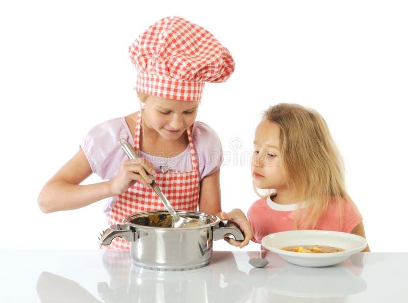 flickor little förberedande soup royaltyfri foto