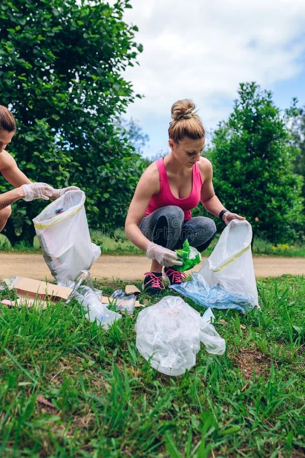 Flickor med avskrädepåsen som gör plogging arkivbild