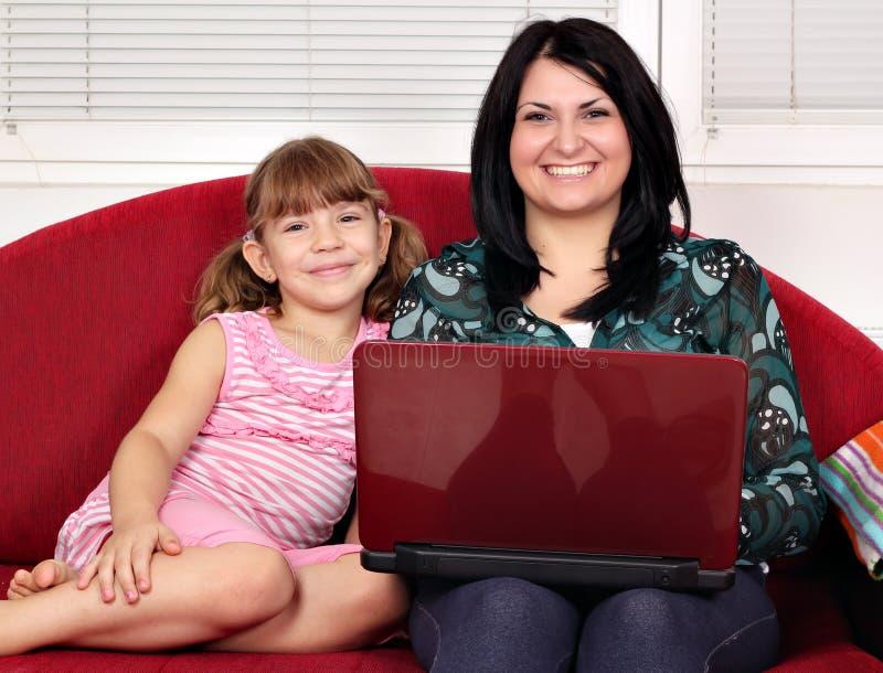 Flickor med bärbar datorsammanträde på säng arkivbilder