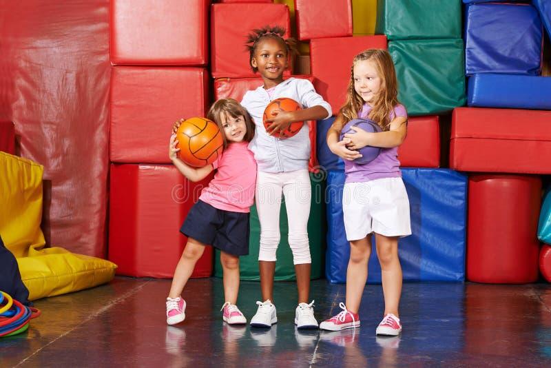 Flickor med bollar i idrottshall av förträningen royaltyfri bild