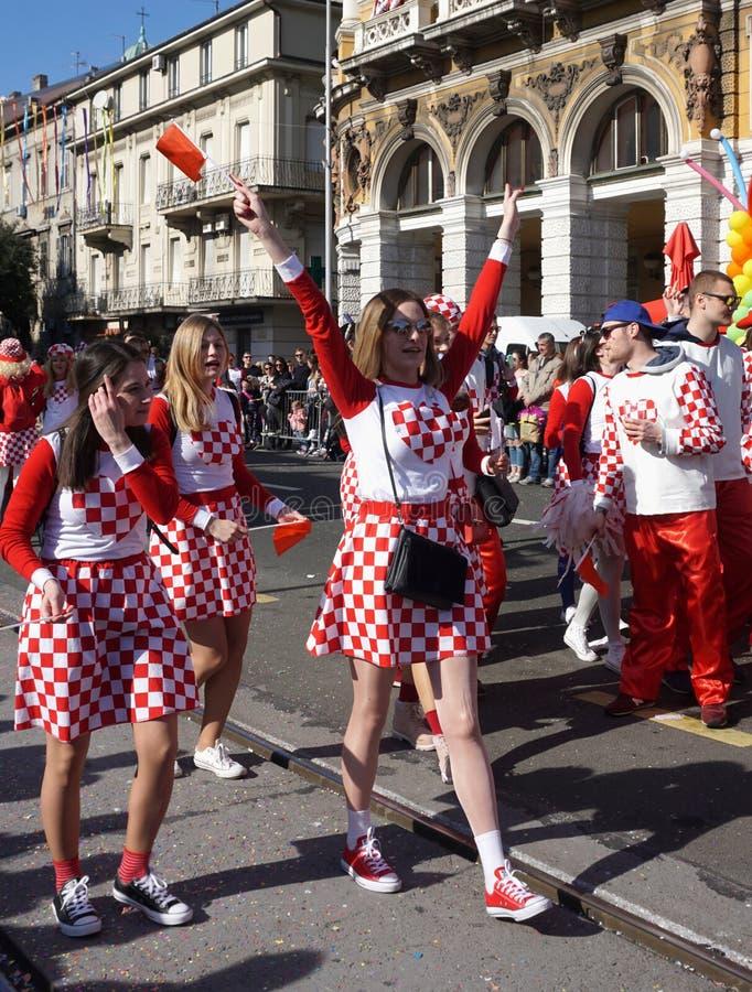 Flickor med den nationella kroatiska symboldräkten och att sjunga och att fira i gatan av staden Rijeka på karnevalprocessionen royaltyfria bilder