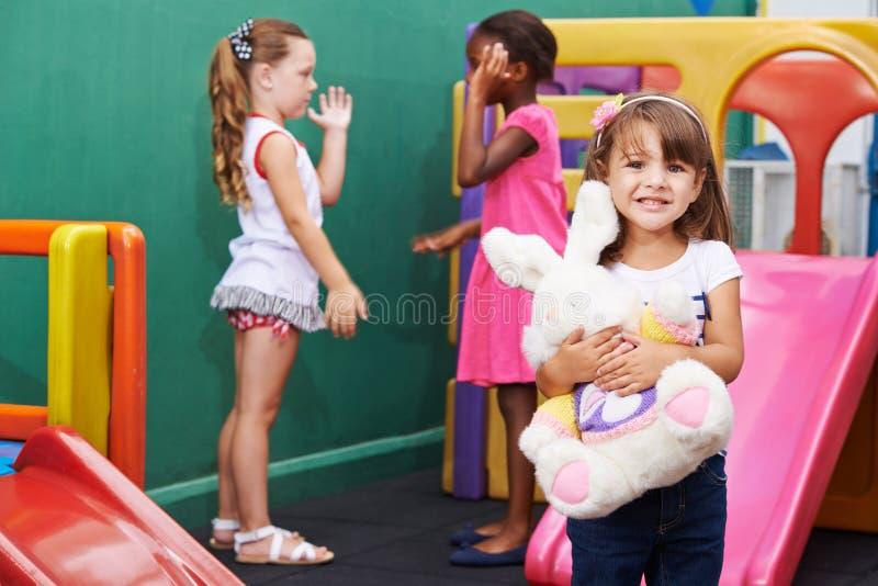 Flickor med det välfyllda djuret i dagis fotografering för bildbyråer