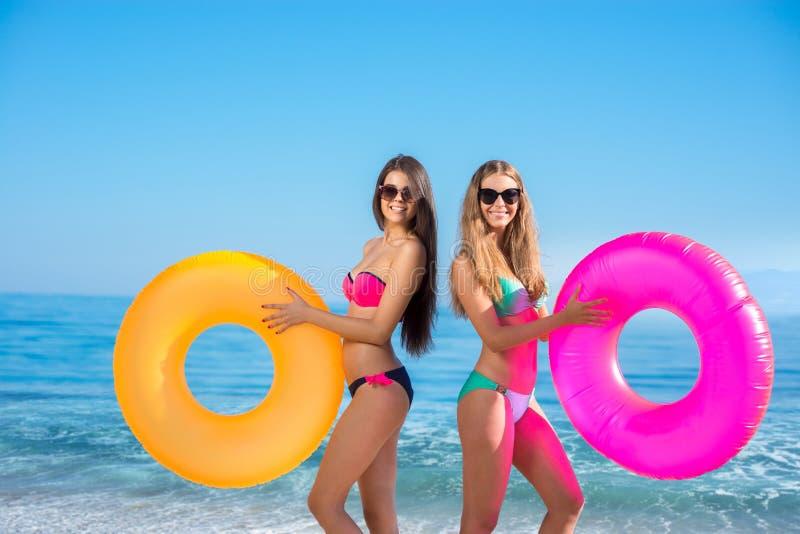 Flickor med rubber cirklar på semesterorten royaltyfri foto