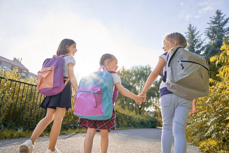 Flickor med ryggsäcken ska skola royaltyfria bilder