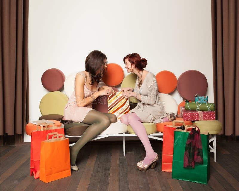 Flickor med shopping hänger lös att skratta royaltyfri foto