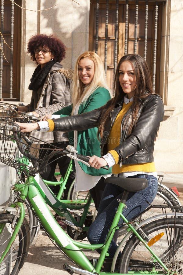 Flickor med stads- cyklar arkivbilder