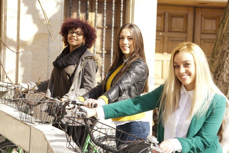 Flickor med stads- cyklar fotografering för bildbyråer