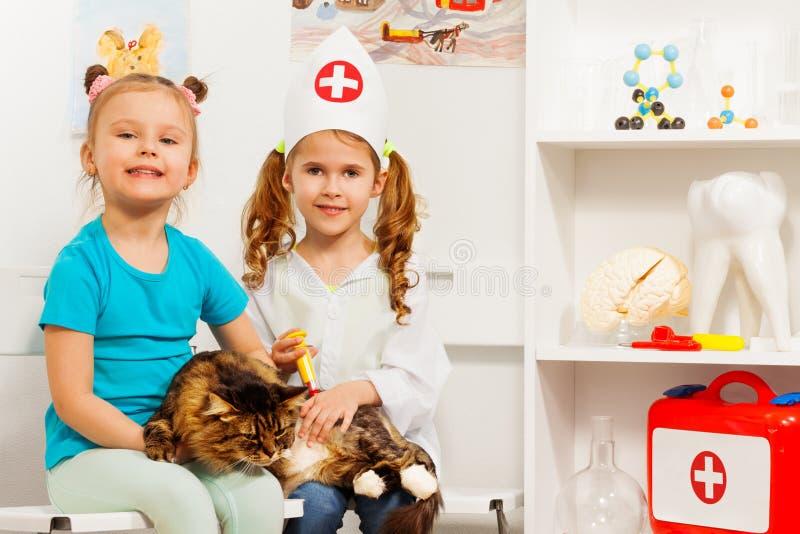Flickor och katt på det veterinär- få en vaccin royaltyfri fotografi