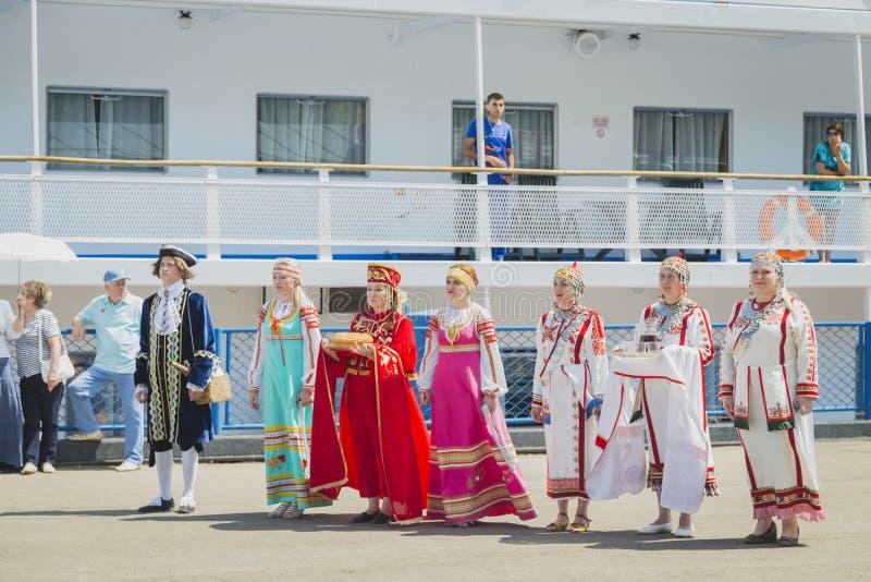Flickor och kvinnor i nationella klänningar mötte passagerare från skeppet royaltyfri foto