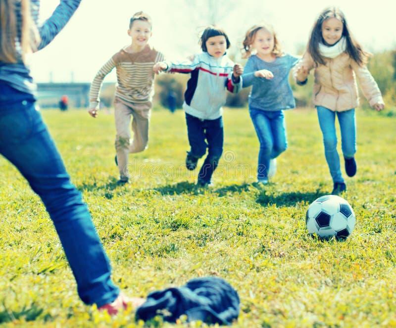 Flickor och pojken som spelar fotboll parkerar in, i höst arkivfoton