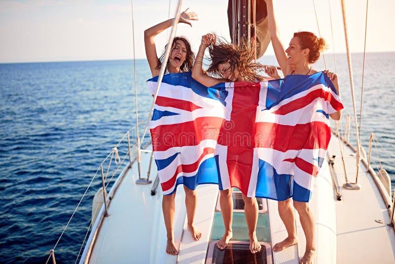 Flickor på yachten i amerikanska flaggan som har partiet - semester, lopp, hav, kamratskap och folkbegrepp royaltyfri foto