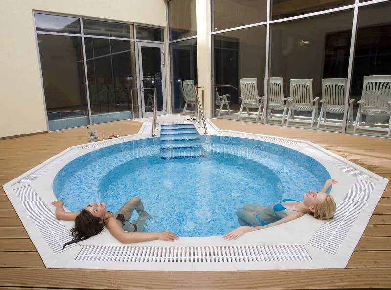 flickor pool att koppla av arkivfoton
