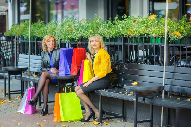 Flickor sitter på en tabell i ett utomhus- kafé med shoppingpackar arkivfoton