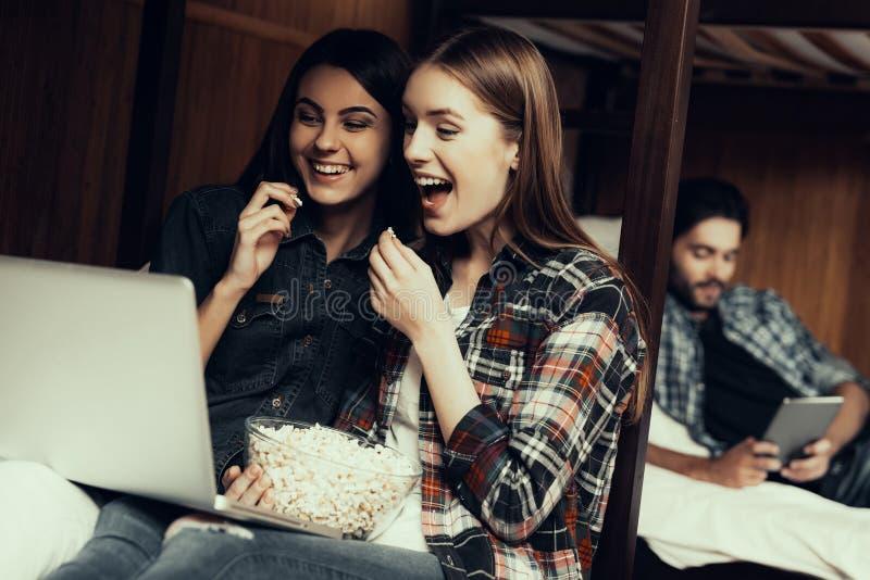Flickor sitter på säng- och hålla ögonen påfilm tillsammans arkivbilder