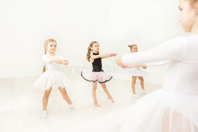 Flickor som öva nära spegeln i balettstudio royaltyfria bilder