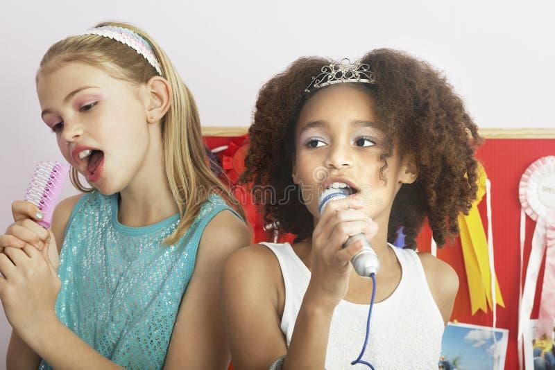 Flickor som använder borstar som mikrofoner på slummerpartiet arkivbilder