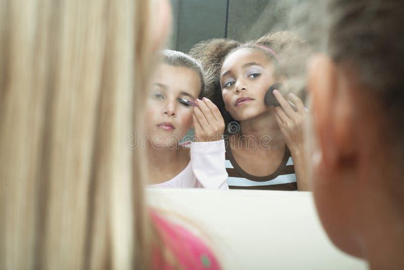 Flickor som applicerar makeup och mascara royaltyfri fotografi