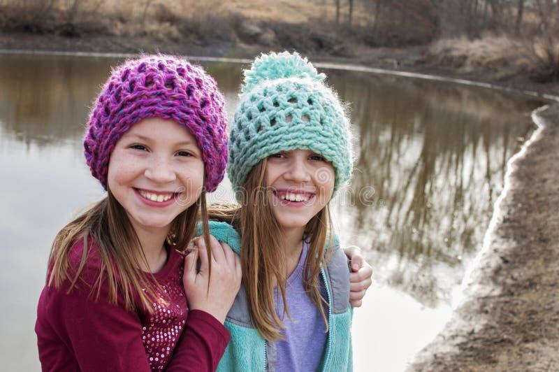 Flickor som bär virkade hattar vid dammet royaltyfri bild
