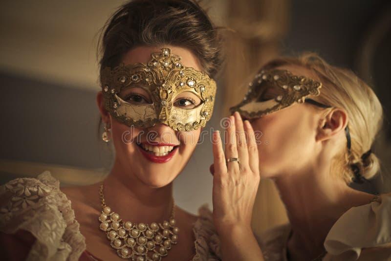 Flickor som berättar en hemlighet i ett karnevalparti royaltyfri fotografi