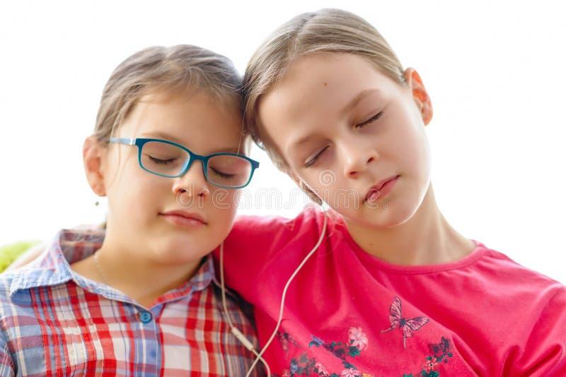 Flickor som delar hörlurar för att lyssna till musik royaltyfria bilder