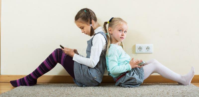 Flickor som direktanslutet spelar med telefoner arkivfoton