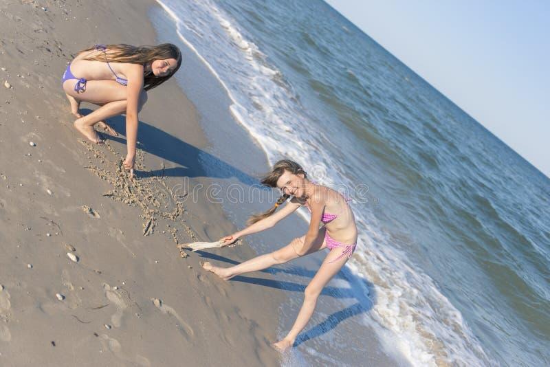 Flickor som drar i sanden på stranden i sommarsolen royaltyfria bilder