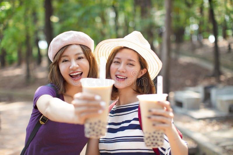 Flickor som dricker bubblate och att tycka om sommarsemester arkivbilder