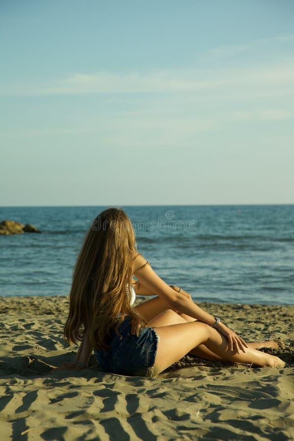 Flickor som framme sitter av havet, i att koppla av för sommar royaltyfria bilder