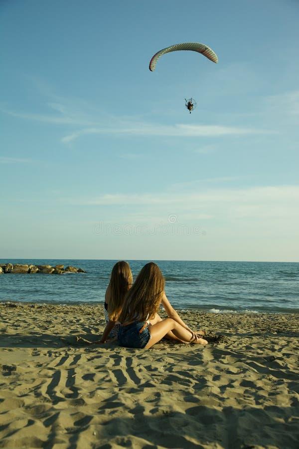 Flickor som framme sitter av havet i avslappnande sned bollskott för sommar royaltyfria foton