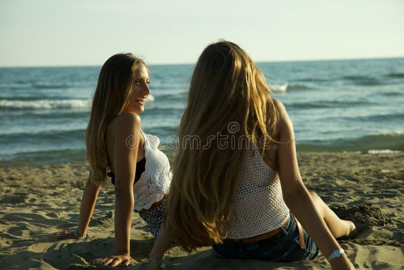 Flickor som framme sitter av havet i sommar som kopplar av att skratta royaltyfri bild