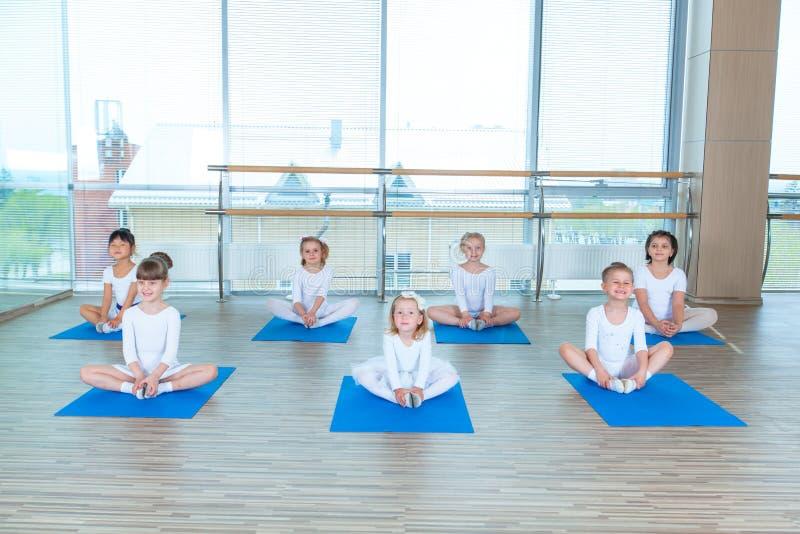 Flickor som gör gymnastiska övningar eller övar i konditiongrupp royaltyfri fotografi