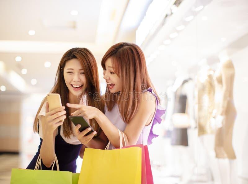 Flickor som håller ögonen på telefonen och shoppar i gallerian royaltyfri bild