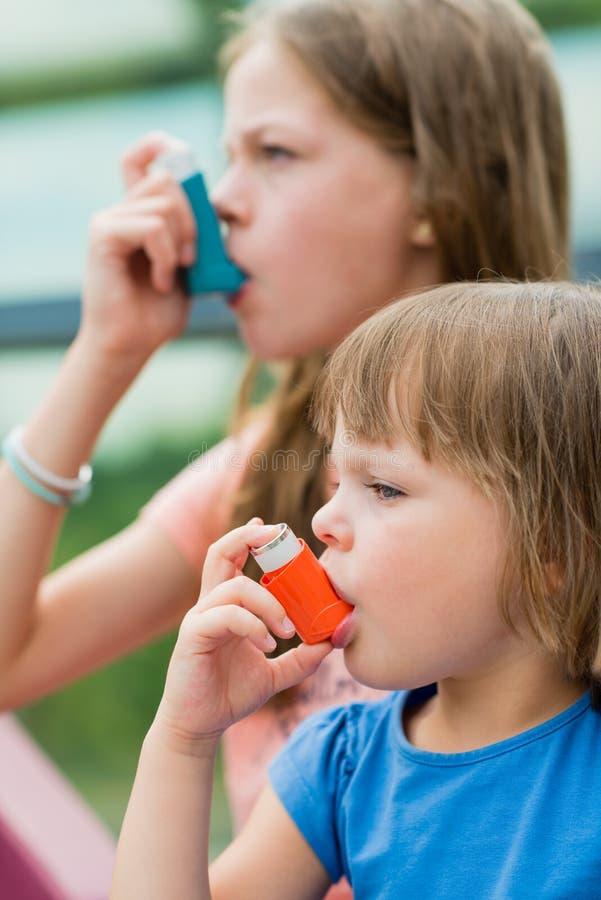 Flickor som har astma genom att använda astmainhalatorn för att vara sunt - sha arkivbild